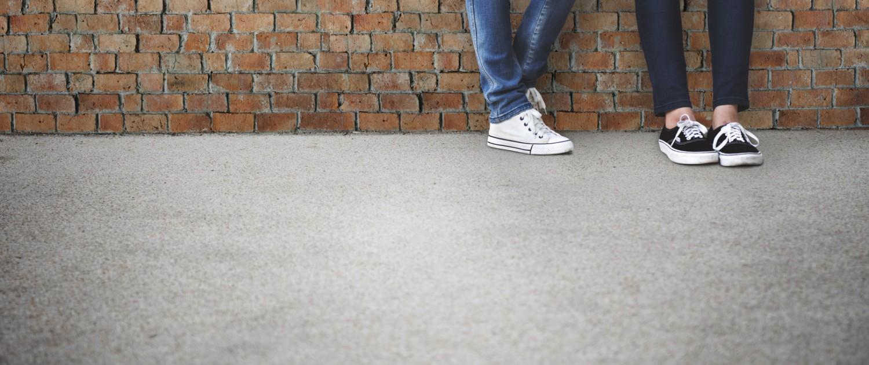 Füsse von zwei jungen Personen an einer Ziegelmauer stehend