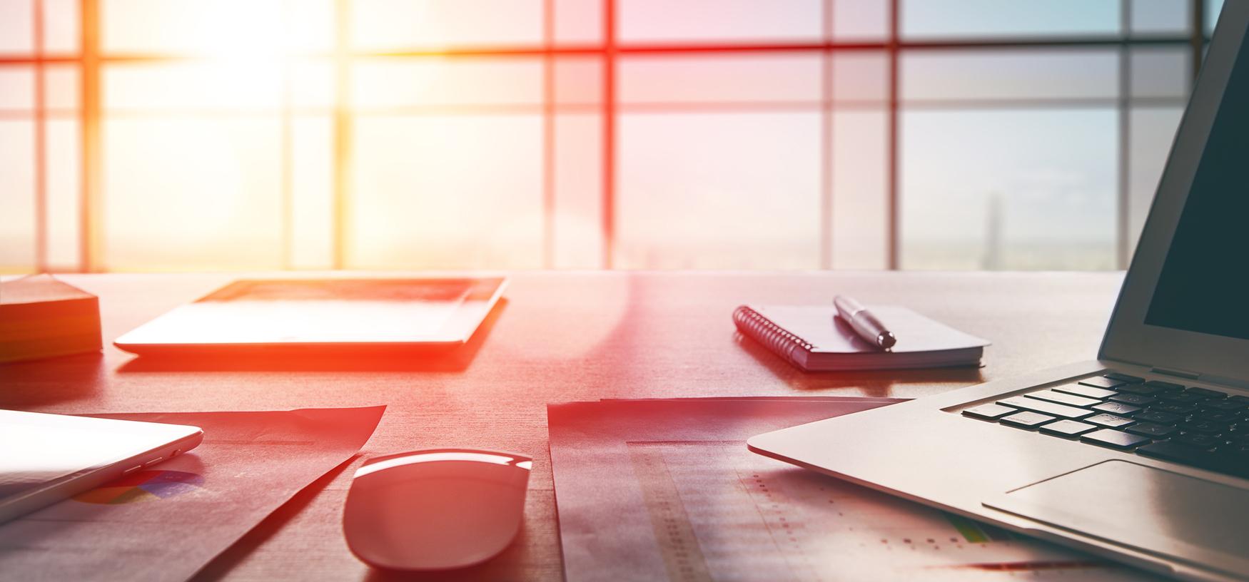 Büroarbeitsplatz mit Notebook auf Holztisch im Gegenlicht vor Fenster