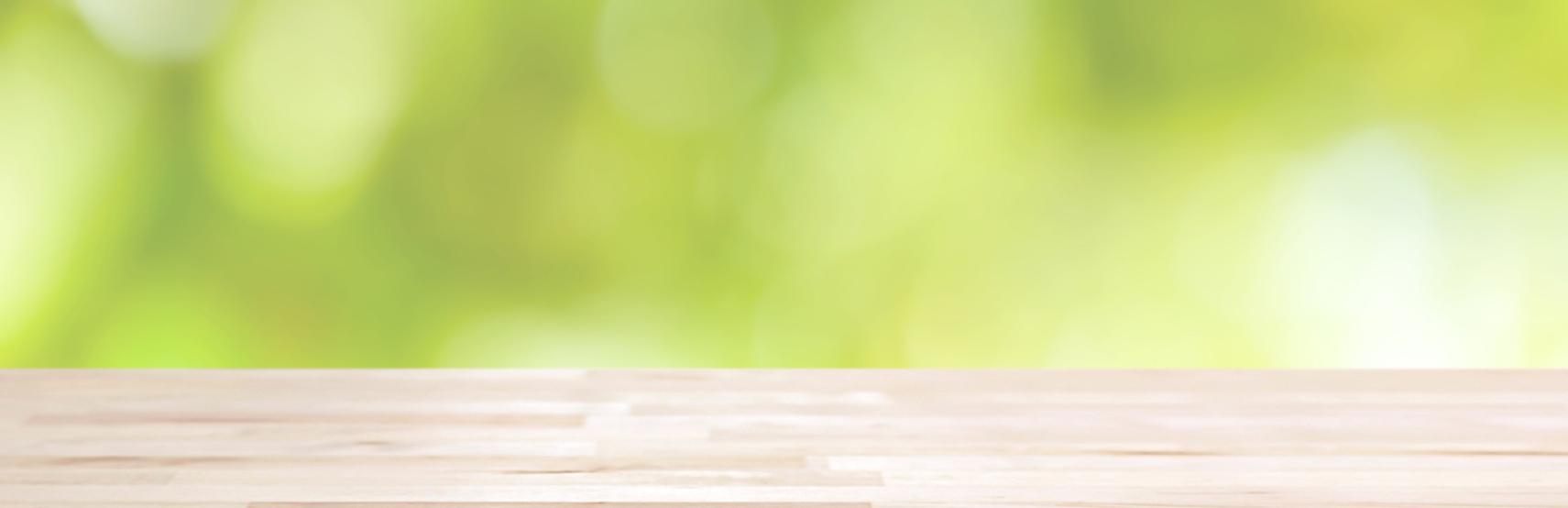 heller Holztisch auf abstrakten grünen Hintergrund