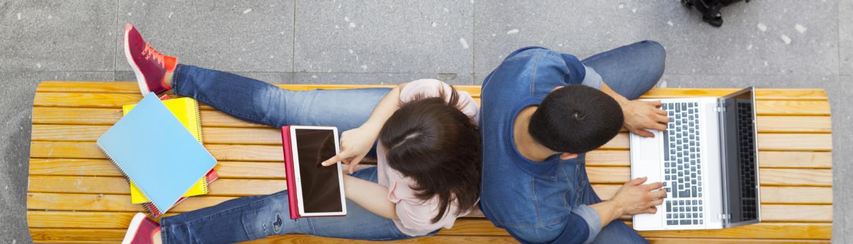 Studenten von oben mit Laptop sitzend