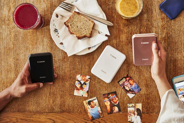 Holztisch mit ausgedruckten Fotostickern und Frühstück und Canon Zoemini Fotodruckern