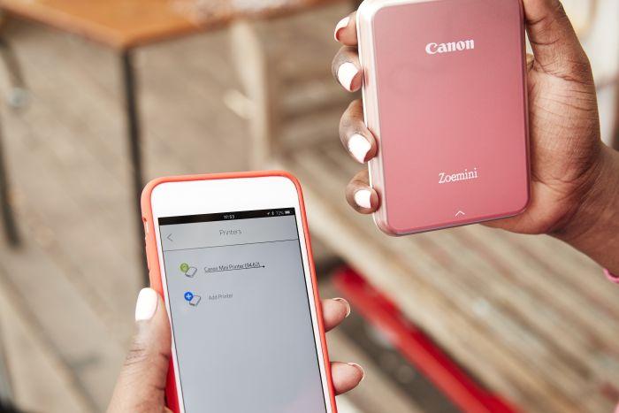 zwei Hände mit Smartphone und Drucker Canon Zoemini rosegold