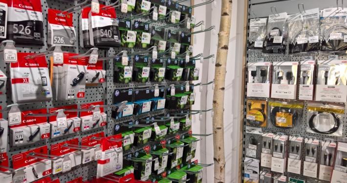 Regal mit EDV Kabeln und Druckertintenpatronen, dazwischen ein Birkenstamm
