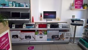 Blick in den Shop mit Teil der Verkaufsregale, Notebooks, Drucker, Zubehör