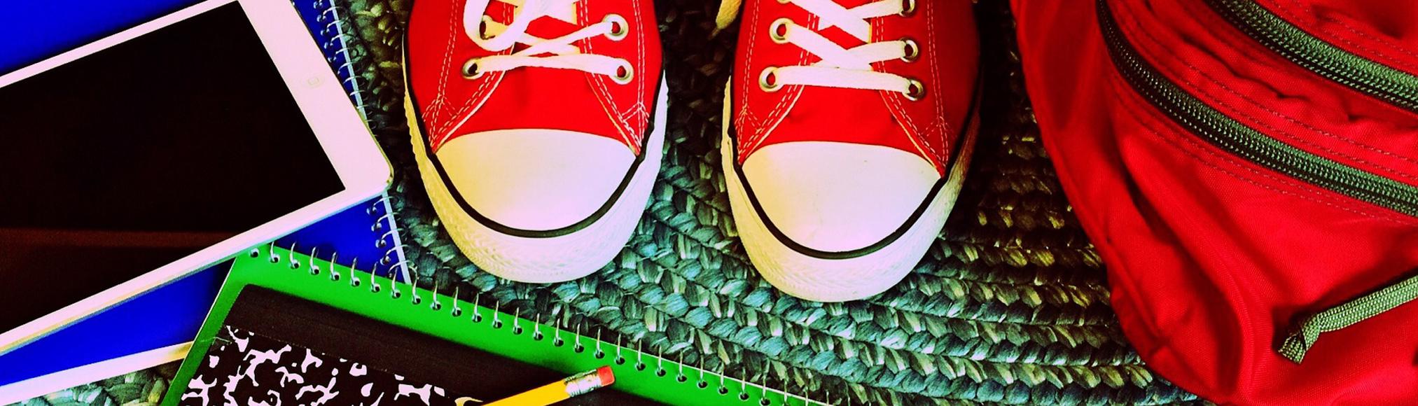 Foto von Schulzeug Rucksack und sneaker in rot, block blau und rosa tablet
